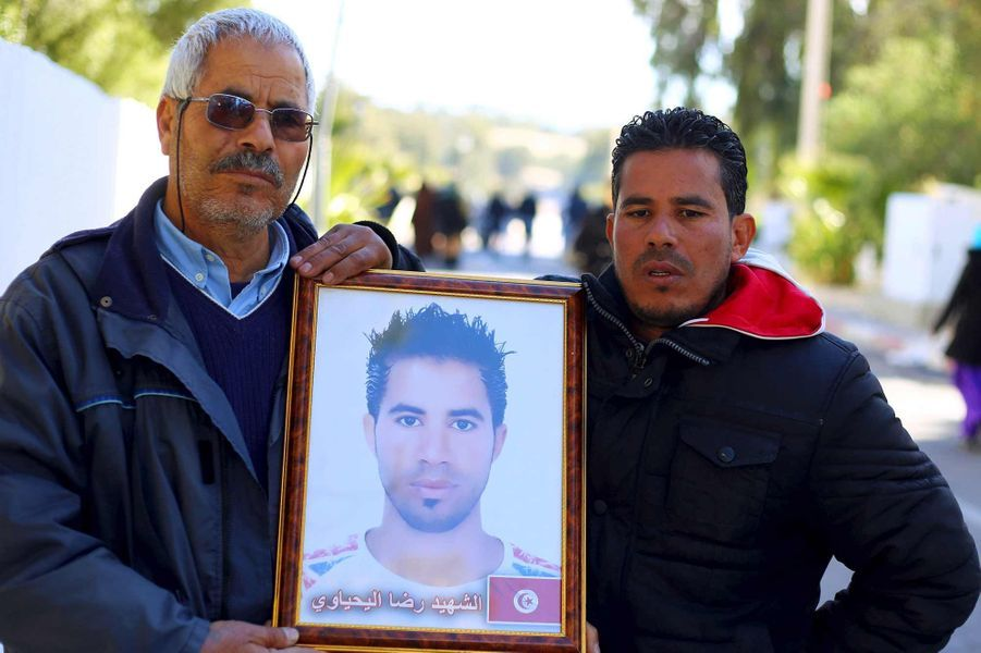 Othman Yahyaoui à G.) brandit un portrait de son fils Ridha Yahyaoui