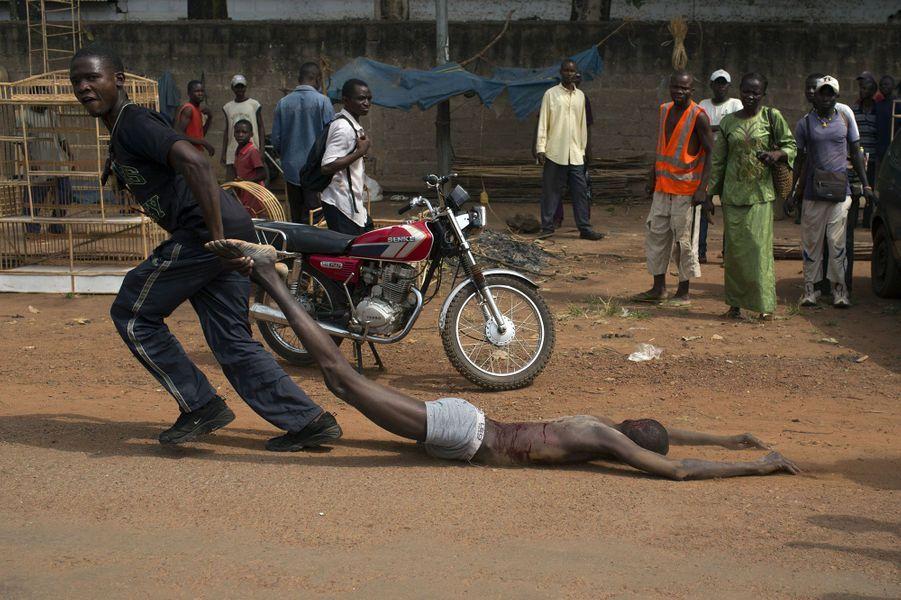 Attention images choquantes. Scène d'extrême violence à Bangui. Soupçonné d'être un combattant de la Seleka, l'armée des rebelles, un homme a été accusé, tué puis mutilé par les FACA (Forces armées centrafricaines). Cet évènement terrible a eu lieu quelques minutes après la venue de la Présidente par intérim, Catherine Samba Panza au Collège National de l'administration et de la magistrature. Elle y demandait le retour de l'ordre et la renaissance de l'armée nationale.