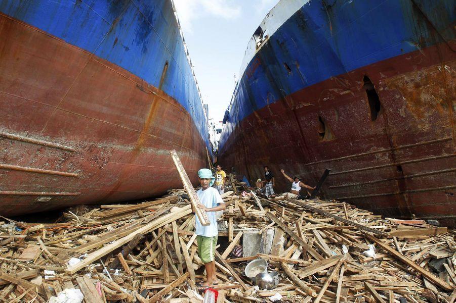 A Tacloban, ces habitants cherchent du bois parmi les débris. La force des vents a poussé ces deux cargos sur la terre ferme.