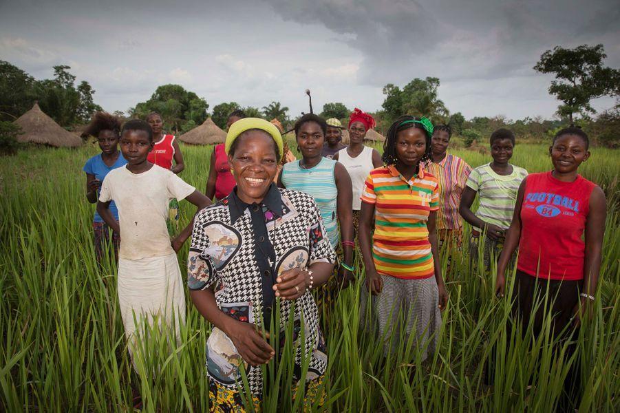 """République démocratique du Congo, 12 mars 2014 --- Angélique NAMAIKA, religieuse catholique de l'ordre des soeurs augustines de Dungu et Doruma, est la lauréate du Prix Nansen décerné par du Haut-commissariat des Nations Unies pour les réfugiés (UNHCR), pour son action auprès des femmes et des enfants victimes des exactions de la LRA, (Lord's Resistance Army), une sanguinaire milice ougandaise pseudo-chrétienne. Dans les herbes près de la""""Maison des Femmes"""" qu'elle a créée, Soeur Angélique pose avec des femmes qu'elle a aidées, qui sont des """"déplacées """"(réfugiées de l'intérieur) et des femmes qui étaient otages de la LRA de Joseph Kony."""