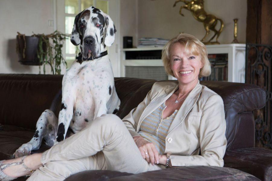 """France, 29 juin 2014 --- Brigitte LAHAIE, ancienne actrice de films pornos, anime depuis 2001 l'émission """"Lahaie, l'amour et vous"""" sur RMC. Elle nous reçoit chez elle dans son domaine des Yvelines. Elle pose ici dans son salon avec Fantaisy, sa chienne dogue allemand."""