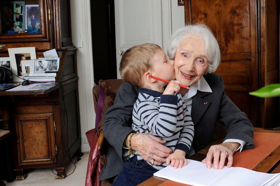 Gisèle CASADESUS a fêté ses 100 ans le 14 juin prochain : attitude souriante de l'actrice dans son appartement du XVIIIème arrondissement avec Axel, son arrière-arrière-petit-fils assis sur genoux, lui donnant un bisou.