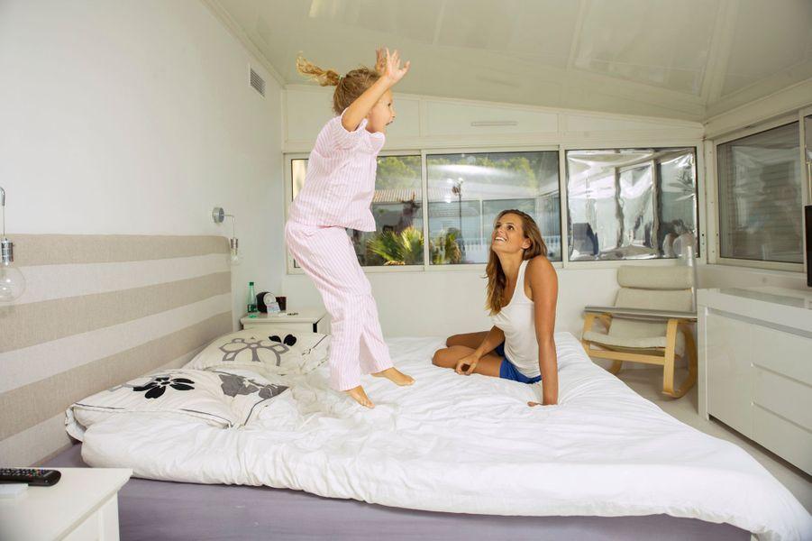 MARSEILLE, vendredi 3 octobre 2014 - attitude souriante de Laure MANAUDOU posant chez elle, regardant sa fille Manon BOUSQUET, 4 ans et demi, en pyjama, sauter sur son lit.