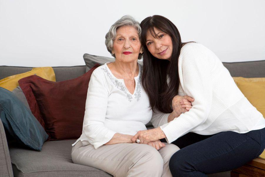 Marie BERRY, atteinte d'une maladie génétique et orpheline, le syndrome d'Alport, reçoit le rein de sa mère Stella à 18 ans. Puis celui de son frère Richard lui est greffé en 2005 à 54 ans, le premier étant en rejet chronique : attitude souriante de Marie posant près de sa mère dans l'appartement de cette dernière à PARIS.