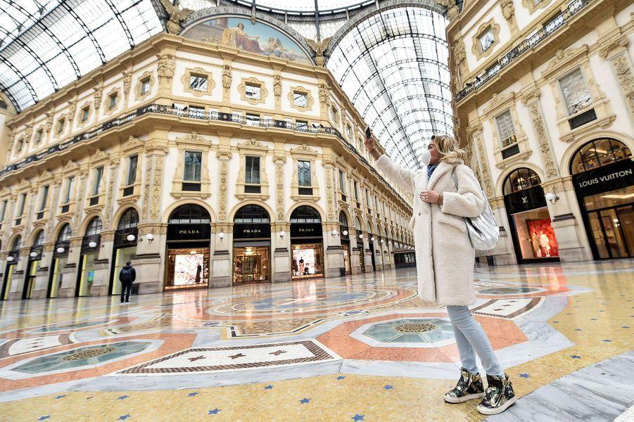 Une femme portant un masque de protection prend un selfie à la Galleria Vittorio Emanuele II, à Milan, en Italie.