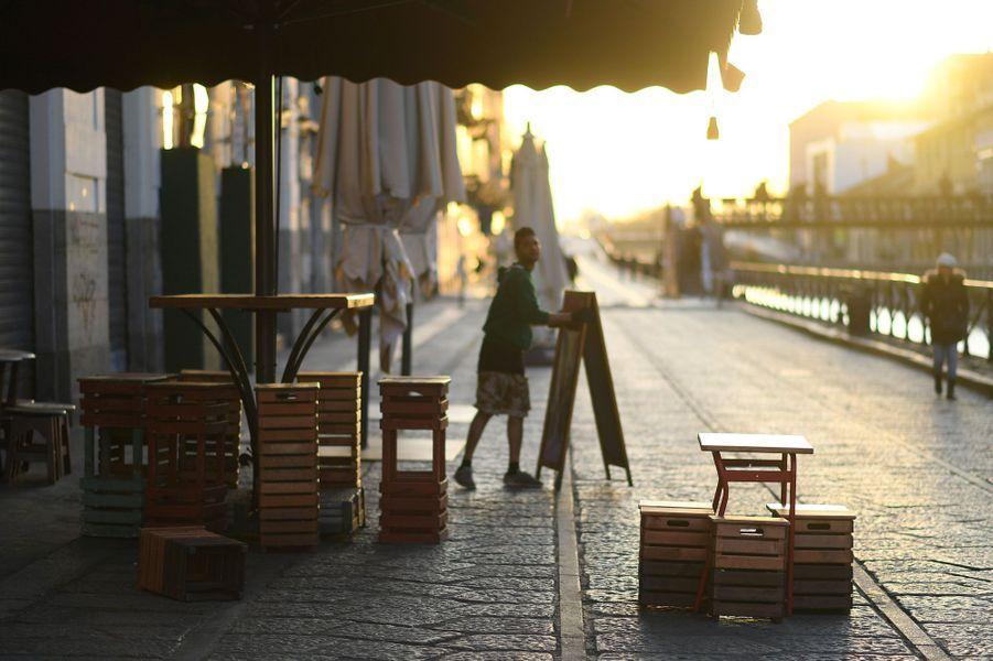 Une personne s'apprête à fermer un restaurant tôt dans le quartier Navigli, à Milan.