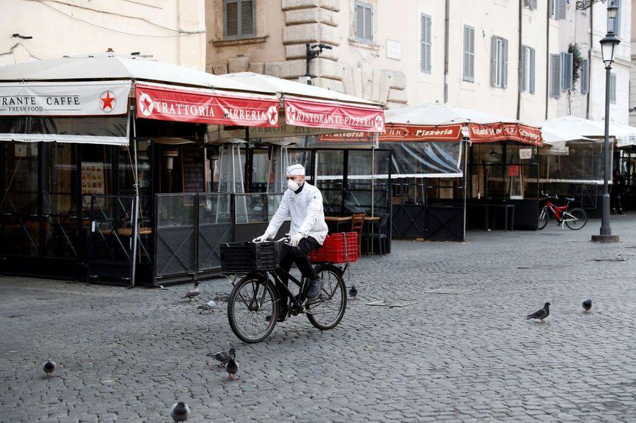 Un livreur porte un masque de protection alors qu'il fait du vélo à Campo de Fiori, à Rome.