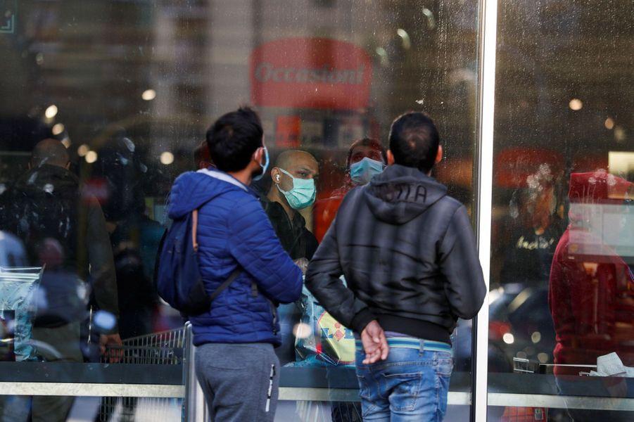 Des gens attendent devant un supermarché pour s'approvisionner en produits alimentaires et en marchandises, à Rome.