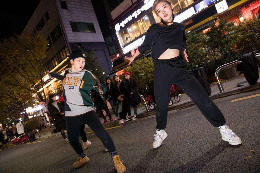 Des groupes de jeunes amateurs de K-pop se produisent tous les vendredis et samedis dans les rues de Hongdae. Ils espèrent ainsi se faire repérer par un producteur.