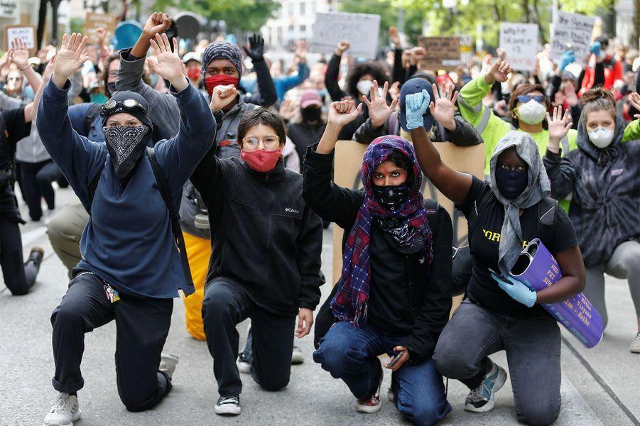 Des manifestant mettent un genou à terre àSeattle.
