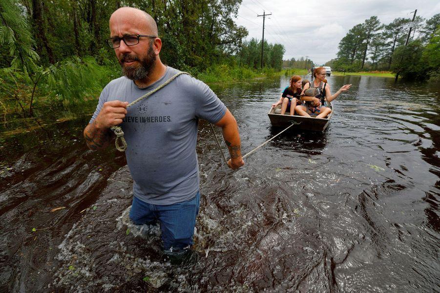 ALeland, ce volontaire tire une barque sur laquelle se tient une mère et ses enfants.