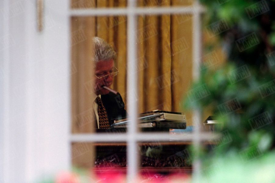 Bill Clinton, cigare à bouche, dans le bureau ovale de la Maison Blanche, le 31 juillet 1998. Trois jours avant, le 28 juillet, Monica Lewinsky, obligée de reconnaitre sa relation avec Clinton face au procureur Kenneth Starr, avait passé un accord provisoire avec lui afin de bénéficier d'un statut d'immunité, en échange de révélations sur ses relations avec le président américain.