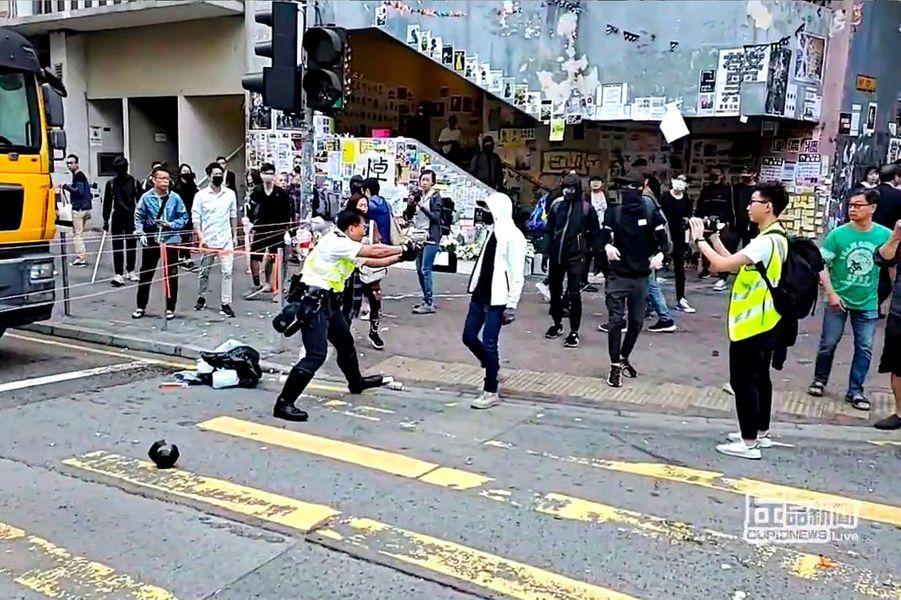 Capture d'écran d'une vidéo montrant un policier qui tire sur un manifestant, lundi à Sai Wan Ho, à Hongkong.
