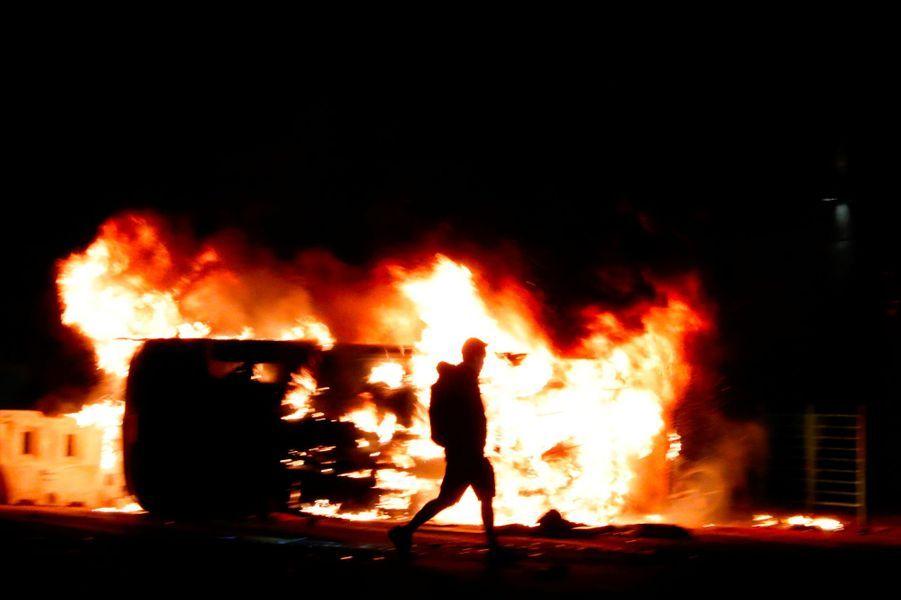 Un manifestant devant un véhicule en feu à Tseung Kwan Ho, à Hongkong, lundi. Attention, les images qui suivent peuvent choquer.