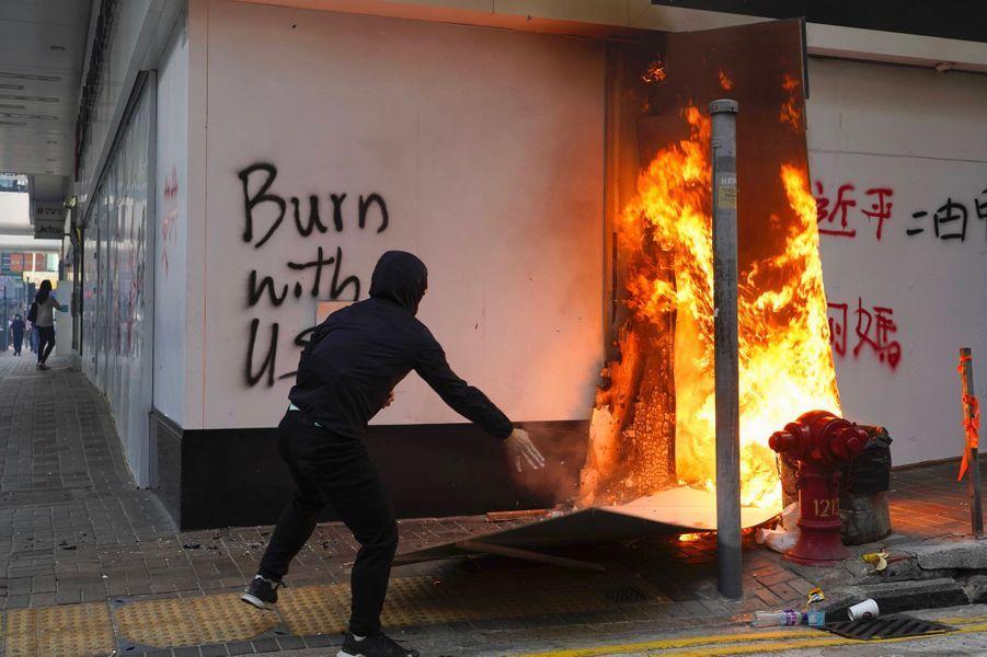 Un manifestant incendie des cartons devant les locaux de la Banque de Chine, dans le centre de Hongkong, lundi. Sur le mur, un slogan : «Brûlez avec nous».