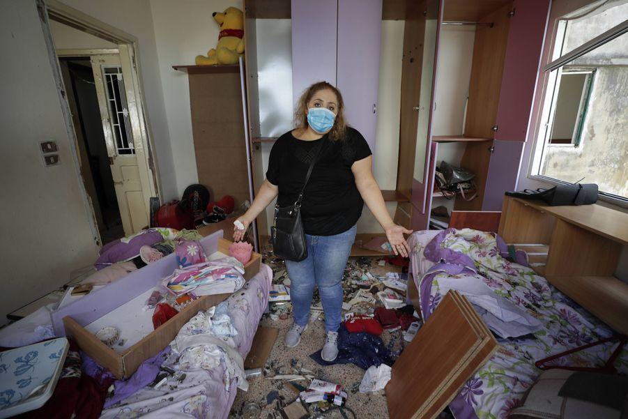 Mona Al Chami pose au milieu de son appartement détruit.