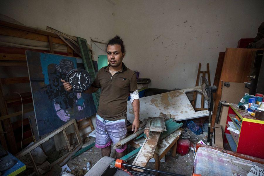 Hasan Al Armali pose dans sa chambre détruite. Il tient une horloge qui s'est arrêtée au moment des déflagrations.