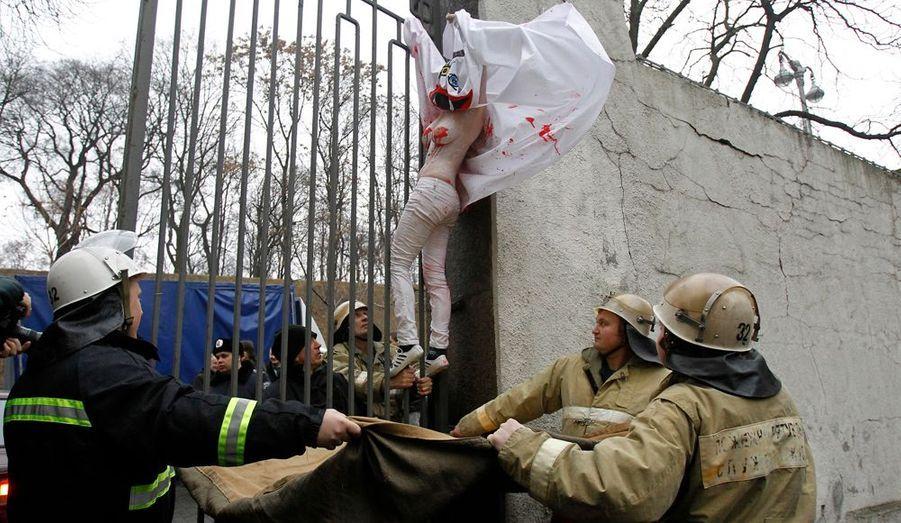 Cette activiste suspendue aux barreaux de la grille d'entrée du gouvernement à Kiev dénonce l'absence de femme au sein du gouvernement ukrainien.