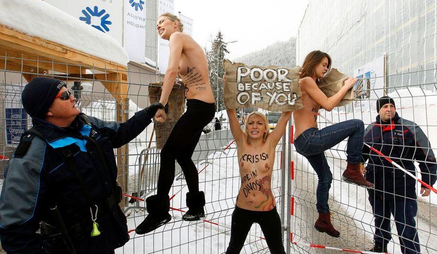 Trois Ukrainiennes du groupe FEMEN ont manifesté devant le poste de contrôle du Forum Economique Mondial (WEF) samedi à Davos en Suisse afin de perturber une rencontre entre patrons de multinationales et politiciens. Les activites ont brandi des pancartes avec les inscriptions «La crise est faite à Davos !» et «Pauvres à cause de vous!».