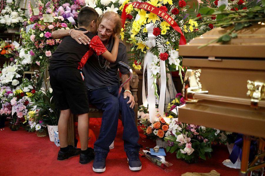 Antonio Basco réconforté par un petit garçon lors des funérailles de sa femme, vendredi au Texas