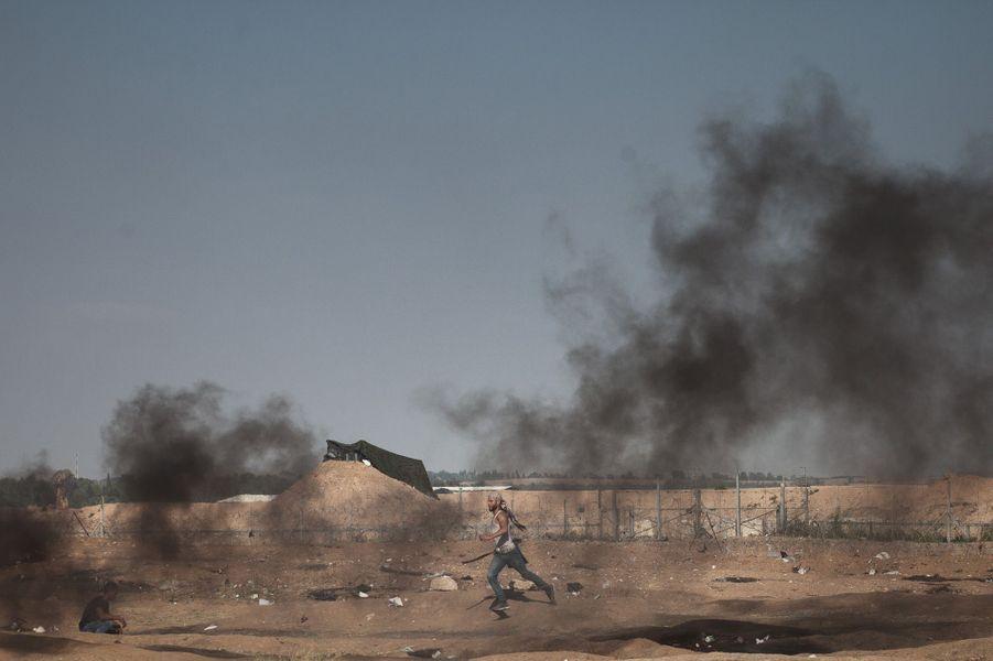 Un jeune homme transporte des pneus enflammés au plus près de la frontière pour couvrir les autres manifestants qui lancent des pierres. Il s'est fait tirer dans la cheville.