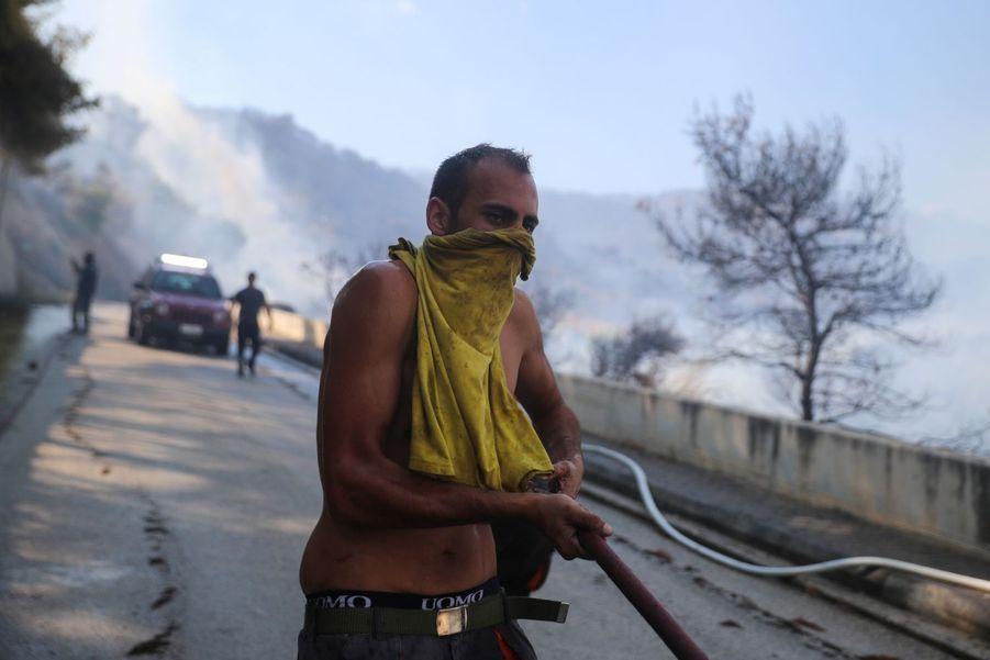 Un homme tient un tuyau pour aider les pompiers à éteindre l'incendie.