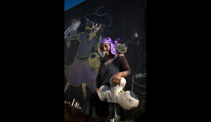 Une Mambo fume de sa pipe bouffarde devant la tombe de la déesse Maman Brigitte, à qui elle rend hommage pendant le rituel du Guédé.