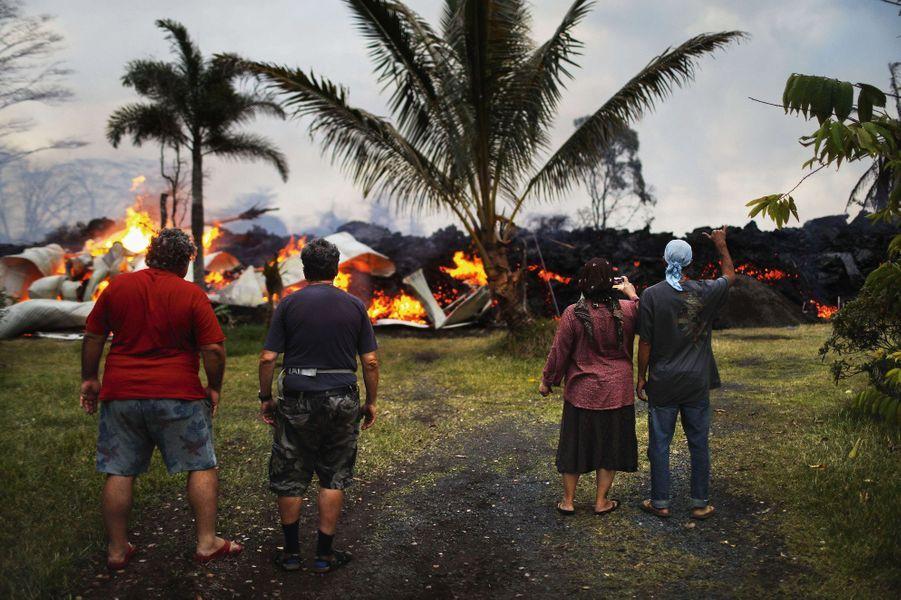 Pahoa, le 25 mai. Les habitants du lotissement de Leilani assistent, impuissants, à la destruction d'une maison par une coulée de lave.