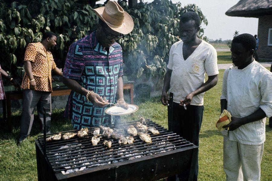 Mobutu et son chapeau texan s'occupe de son barbecue de poisson, Zaïre, 1975.