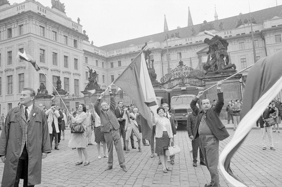 Quelques jours après l'invasion de la Tchécoslovaquie par les troupes du pacte de Varsovie, le reporter de Paris Match Jack Garofalo arpente les rue de Prague occupée. Ici, des civils expriment leur mécontentement et défient les forces de répression en agitant des drapeaux tchécoslovaques, sur la place du Hradschin, devant le Palais.