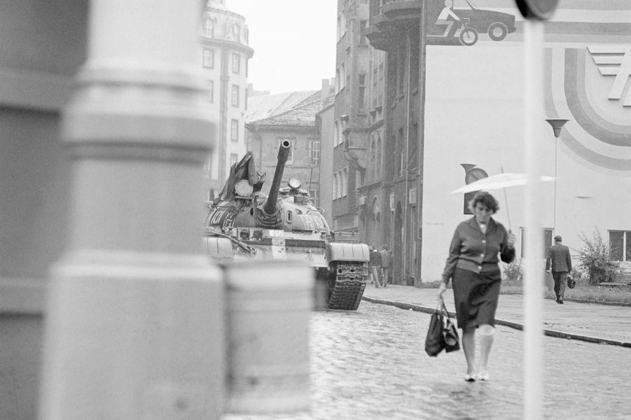 Quelques jours après l'invasion de la Tchécoslovaquie par les troupes du pacte de Varsovie, le reporter de Paris Match Jack Garofalo arpente les rue de Prague occupée. Une femme marchant dans une rue, sous la pluie, suivie d'un véhicule blindé.
