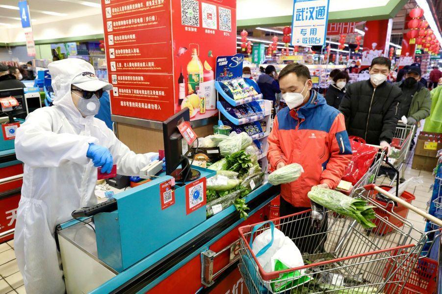 Un caissier dans une combinaison de protection sert des clients dans un supermarché à Wuhan, le 12 février 2020