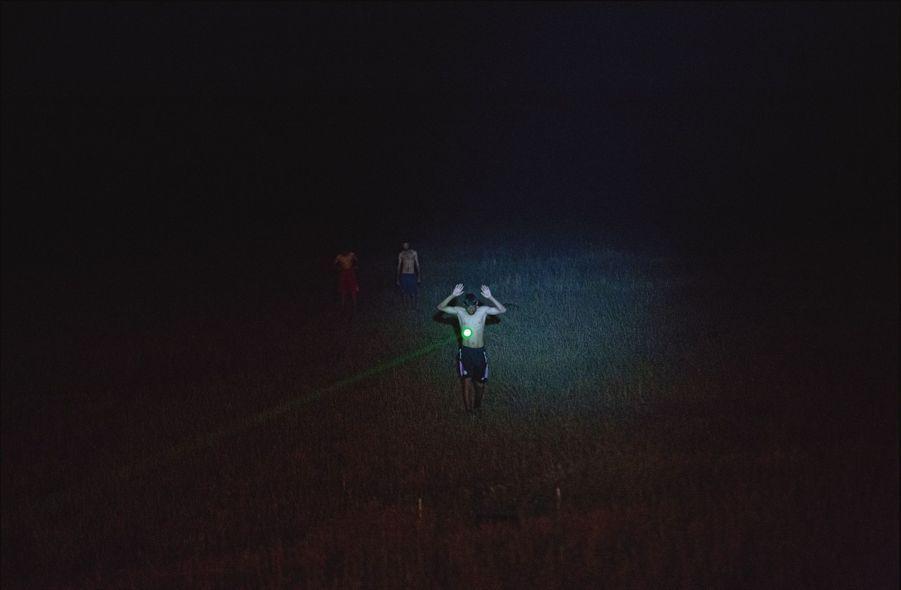 Depuis le haut de la tranchée, un rayon laser est pointé sur un réfugié. L'homme doit lever les bras et tourner sur lui-même avant qu'un soldat s'approche pour le fouiller.