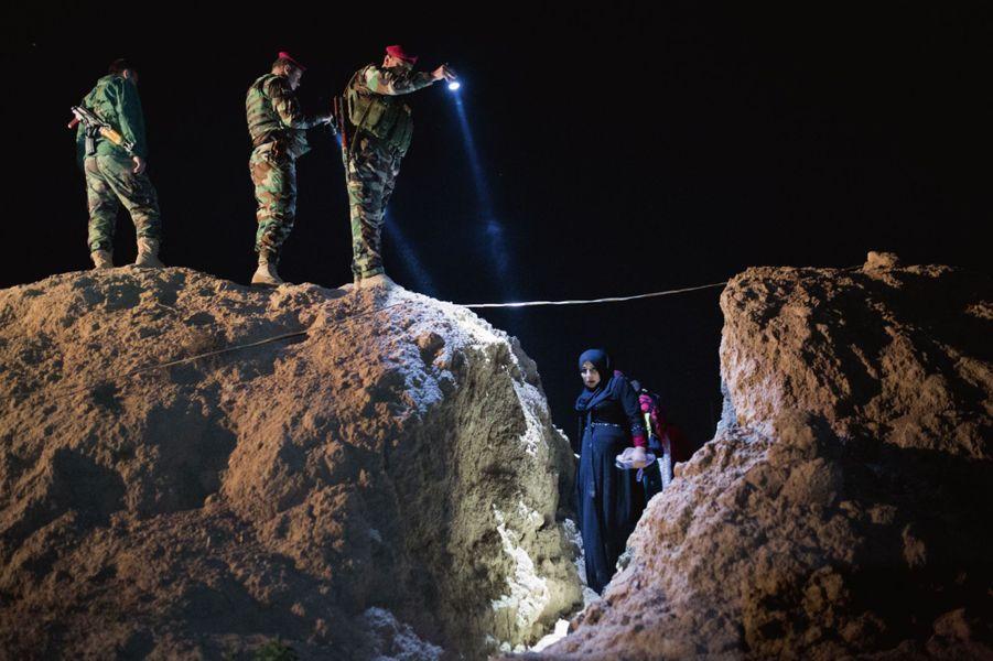 Eclairée par les torches des peshmergas, une femme enceinte franchit la ligne de front à Doogrdkan, 56 kilomètres au sud de Mossoul, le 19 avril, à minuit.
