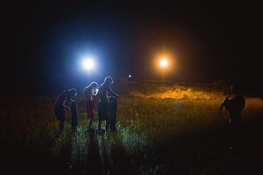 Trois cousins d'une vingtaine d'années se rhabillent sous la surveillance d'un peshmerga. Un champ sépare le site du premier village contrôlé par Daech, à 3 kilomètres.