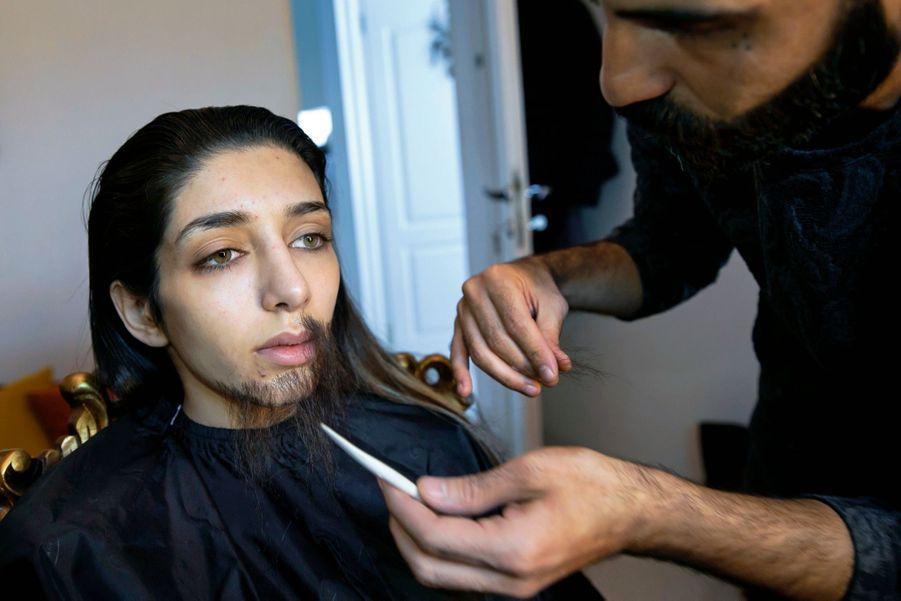 Un ami maquilleur pose une barbe sur le visage triste de Zeinab : pas drôle de devoir dissimuler sa féminité.