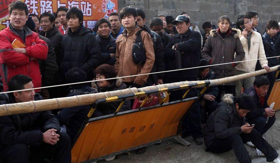 Des personnes attendent pour acheter leurs billets de train à la gare de Shanghaï; Ils sont nombreux à retourner chez eux pour le nouvel an chinois. Certains attendent depuis plus de 30 heures.