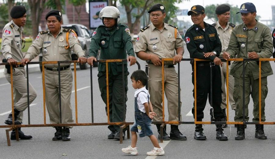 Les policiers cambodgiens regardent un petit enfant passer devant eux lors de la commémoration de la mort de Chea Vichea, un leader syndicaliste du pays assassiné il y a cinq ans.