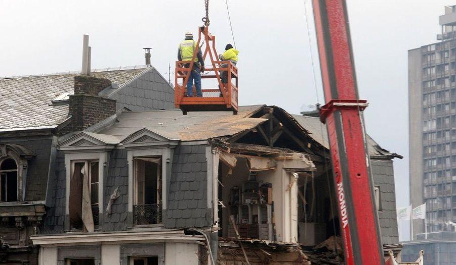 Des experts inspectent les dégâts causés par un explosion de gaz dans Liège. Une partie de l'immeuble s'est effondrée sous la violence du choc.