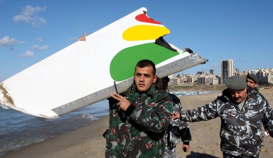 Un policier porte un morceau d'une aile, trouvé sur une place de Beyrout, de l'avion de la compagnie Ethiopian Airlines qui s'est abîmé lundi matin dans la mer Méditerrannée.