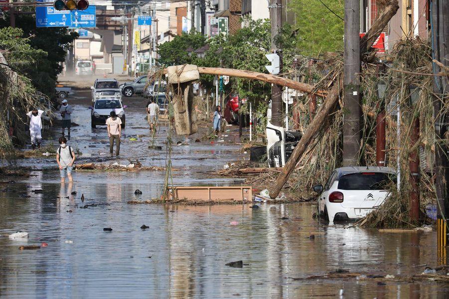 Les inondations dans la région de Kumamoto ont détruit des maisons, emporté des véhicules et provoqué l'effondrement de ponts, laissant de nombreuses villes sous les flots et certains habitants coupés du monde.