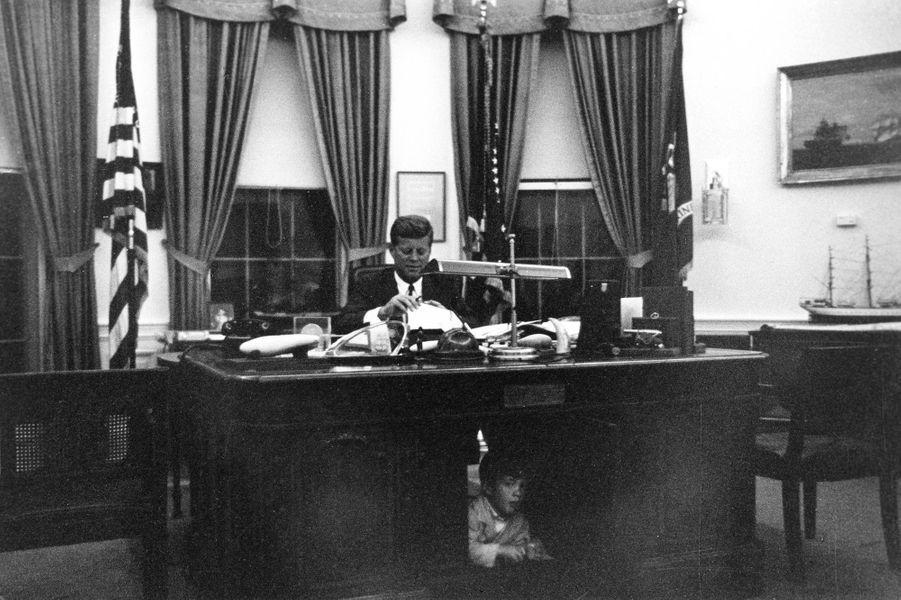 John F. Kennedy dans le Bureau ovale, en octobre 1963. Sous le bureau du résolu, son fils John John.