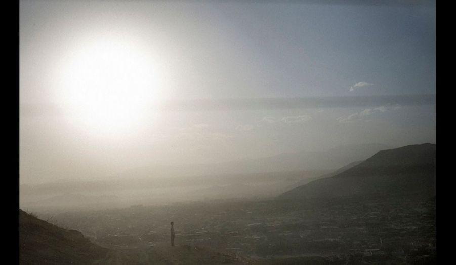 Sur les hauteurs de Kaboul, un jeune garçon observe la ville.