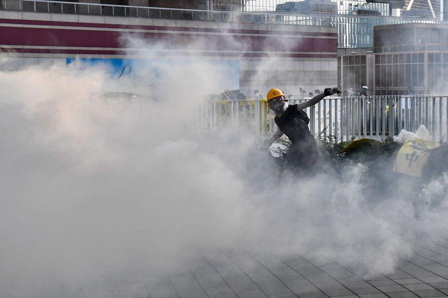 Dans le quartier du gouvernement de Hong Kong, des manifestants sous les lacrymogènes, lundi.