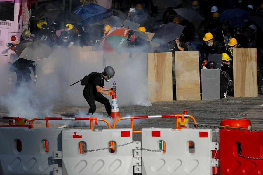 Dans le quartier du gouvernement, un manifestant place un plot sur une grenade lacrymogène, lundi à Hong Kong.