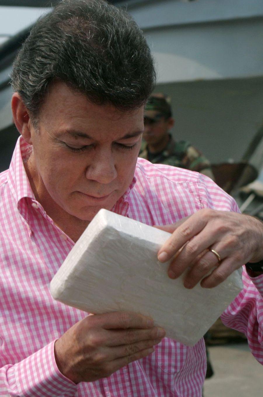 Juan Manuel Santos, alors ministre de la Défense, observe un bloc de cocaïne saisi à Carthagène, en mars 2007.