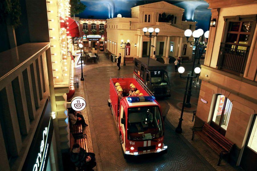 Le camion de pompiers file vers un incendie. Au fond : une reconstitution du théâtre Bolchoï.
