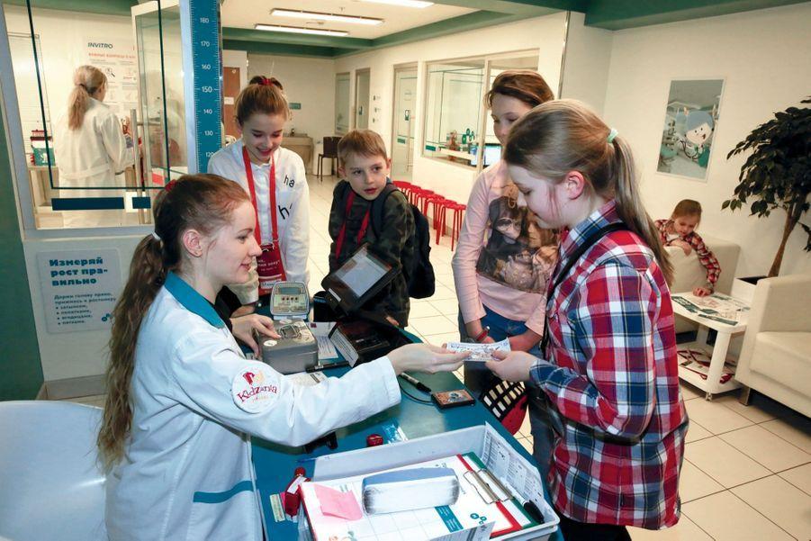 2. Dans l'hôpital, une animatrice distribue leur salaire aux membres de l'équipe médicale.