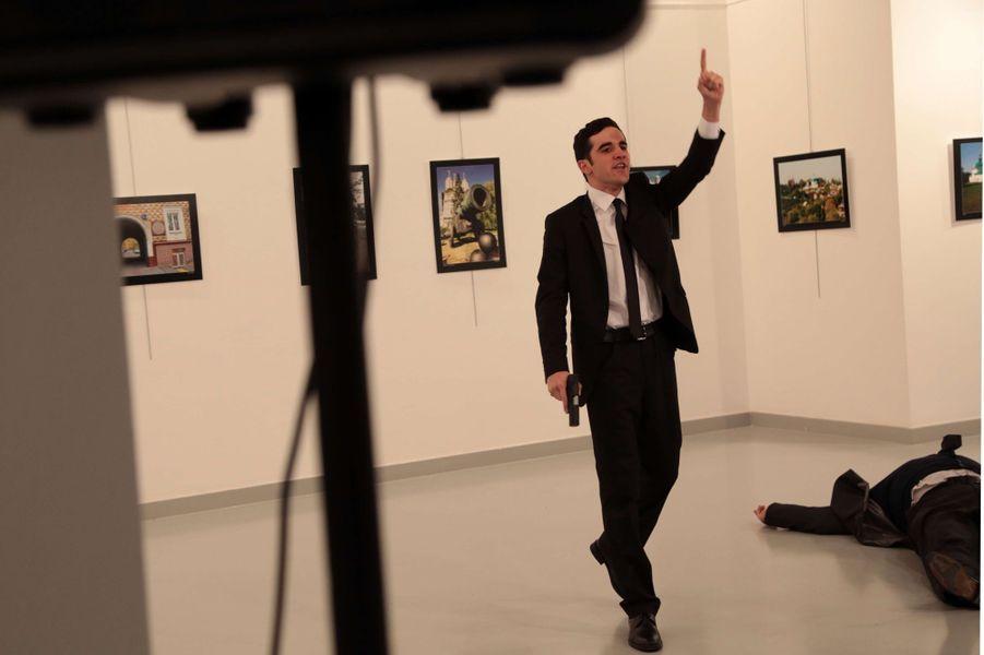 """L'ambassadeur de Russie en Turquie a été tué lundi dans un attentat """"terroriste"""" perpétré par un homme armé qui a évoqué une vengeance pour la ville syrienne d'Alep.L'homme (derrière l'ambassadeur sur cette photo) qui a ouvert le feu sur le diplomate, Andreï Karlov, pendant qu'il visitait une exposition d'art à Ankara, était """"de la police"""", a déclaré le maire d'Ankara, Melih Gökçek."""