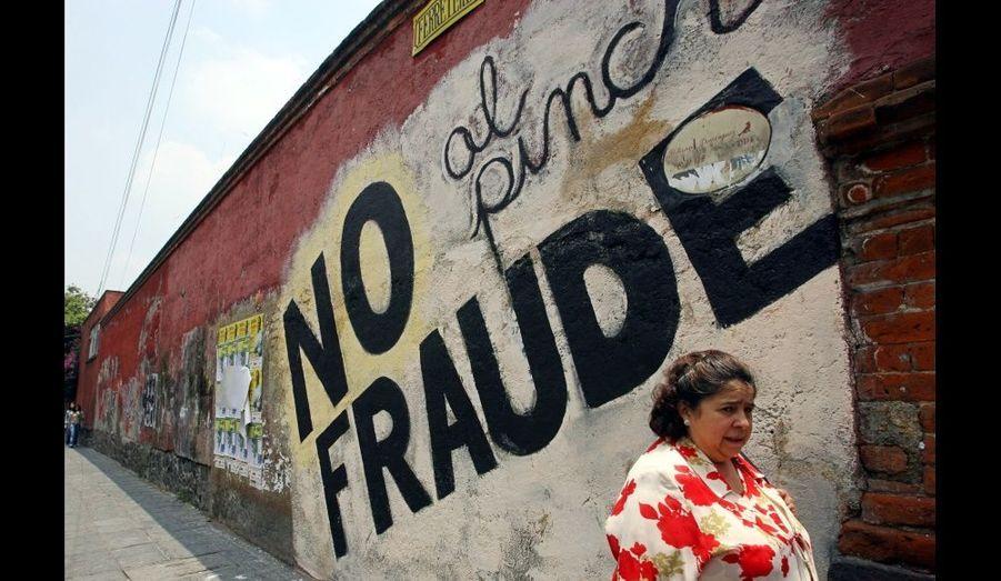 """Une femme passe devant l'inscription """"No Fraud"""", après les élections début juillet à Mexico."""